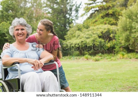 Granddaughter embracing grandmother in wheelchair in the park on sunny day - stock photo