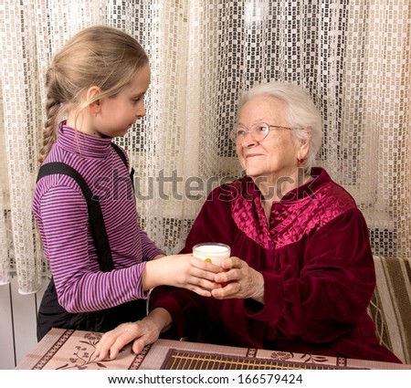 Granddaughter giving glass of milk to grandmother - stock photo