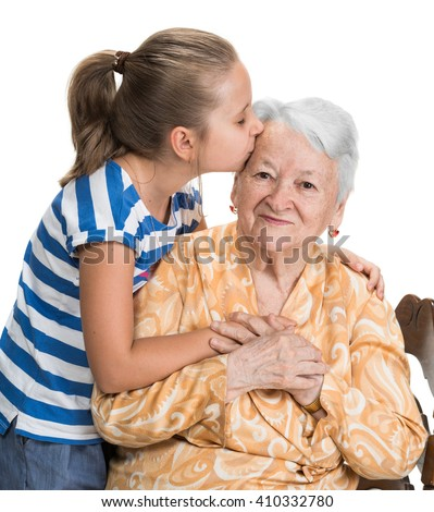 Granddaughter kissing her old grandmother on white background - stock photo
