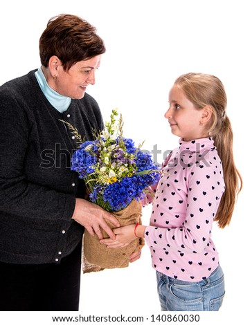Granddaughter presenting bouquet of  wildflowers to her grandmother on a white background - stock photo