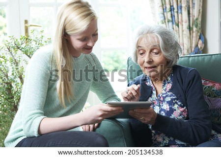 Granddaughter Showing Grandmother How To Use Digital Tablet - stock photo