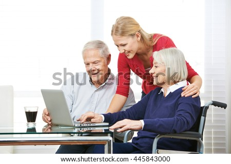 Granddaughter showing senior people online computer use - stock photo