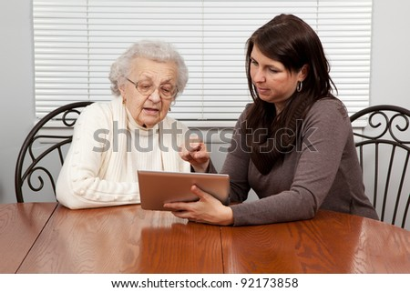 Granddaughter Teaching Grandmother How to Use a Tablet PC - stock photo