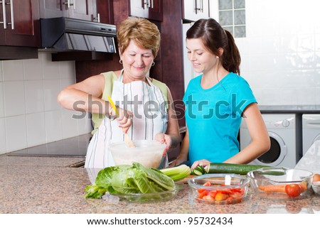 granddaughter watching grandma cooking in kitchen - stock photo