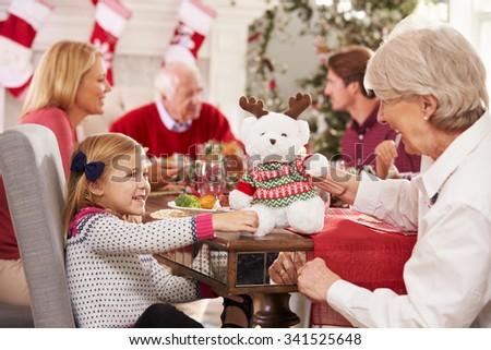 Granddaughter With Grandmother Enjoying Christmas Meal - stock photo