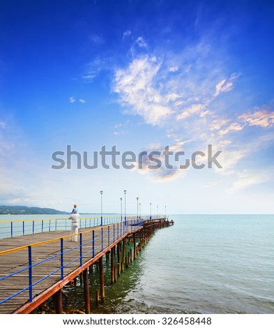 Grandfather and girl are on the dock at the seaside - stock photo