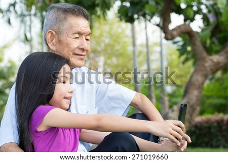 Grandfather and grandchild making self portrait with smart phone in the park - stock photo