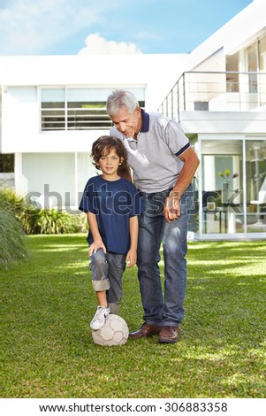 Grandfather and grandchild playing soccer in garden in front of a house
