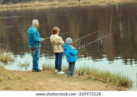 Grandfather and grandchildren are fishing - stock photo