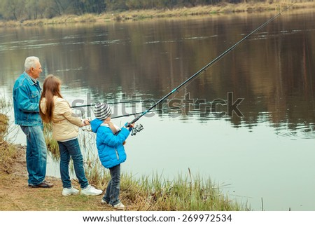 Grandfather and grandchildren are fishing - stock photo