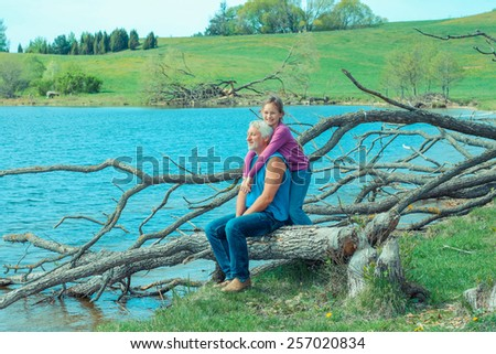 Grandfather and granddaughter are dreaming in nature. Grandfather and granddaughter enjoy the open spaces in nature.   - stock photo