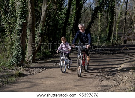 Grandfather and granddaughter cycling together