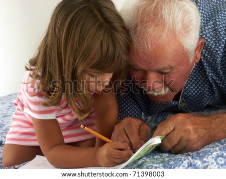 grandfather and granddaughter drawing and reading in a bed. - stock photo