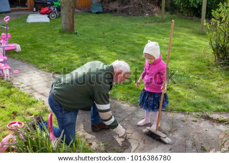 grandfather and granddaughter  in the graden pulling up weeds