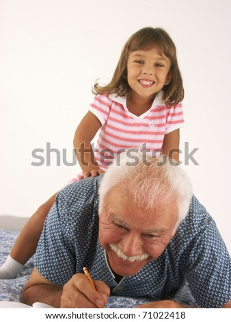 Grandfather and granddaughter playing at home. - stock photo