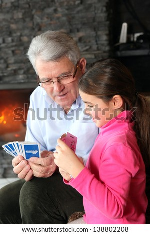 Grandfather and granddaughter playing cards - stock photo