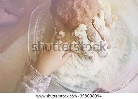 Grandfather and granddaughter preparing dumplings together, photo toning Pastel - stock photo