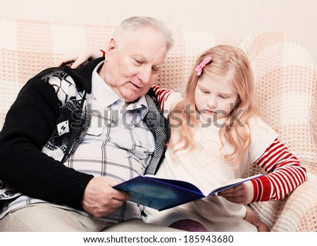 grandfather and granddaughter sitting on the sofa and reading book - stock photo
