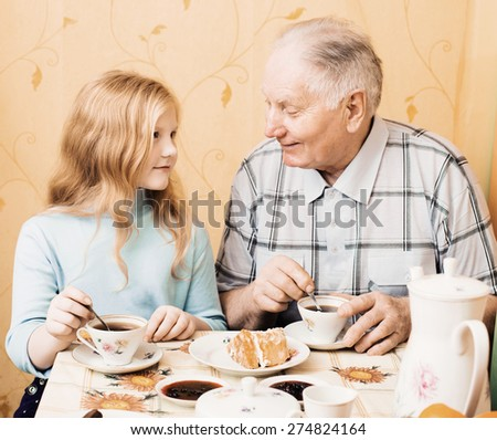grandfather and granddaughter sitting on the table in kitchen - stock photo