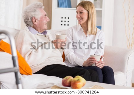 Grandfather and granddaughter smiling, talking and drinking tea - stock photo