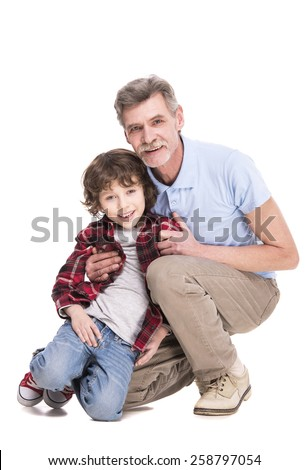 Grandfather and grandson are hugging and looking at the camera on white background.