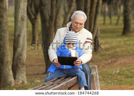 Grandfather and grandson are looking tablet on bench outdoors - stock photo