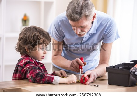 Grandfather and grandson are measuring a board with measuring tape.