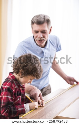 Grandfather and grandson are measuring a table with measuring tape.