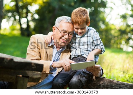 Grandfather and grandson are using digital tablet in park - stock photo