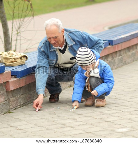 Grandfather and grandson draw with chalk on the road