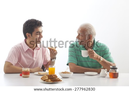 Grandfather and grandson eating breakfast - stock photo