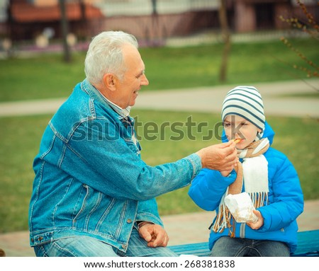 Grandfather and grandson eating fries and indulge - stock photo
