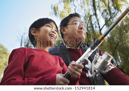 Grandfather and grandson fishing portrait - stock photo