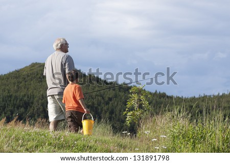 Grandfather and Grandson Going Fishing: With backs turned to the camera, grandfather and grandson walk over a field with a fishing rod and bucket. - stock photo