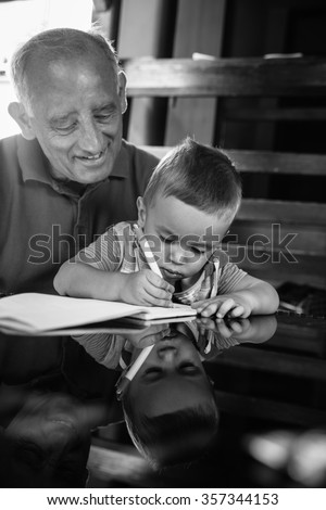 Grandfather and grandson having fun drawing something on paper on a glass table.Black and white.