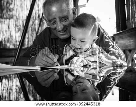 Grandfather and grandson having fun drawing something on paper on a glass table that reflects their faces.Black and white. - stock photo