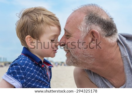 Grandfather and grandson having fun on the beach - stock photo