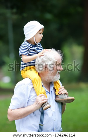 Grandfather and grandson having fun outdoors - stock photo