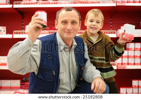 Grandfather and grandson in food shop - stock photo