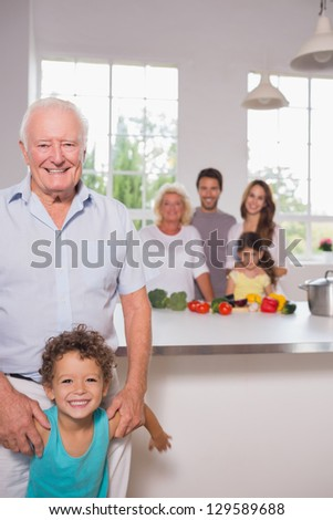 Grandfather and grandson in front of their family in the kitchen - stock photo