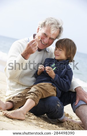 Grandfather And Grandson Looking at Shell On Beach Together - stock photo