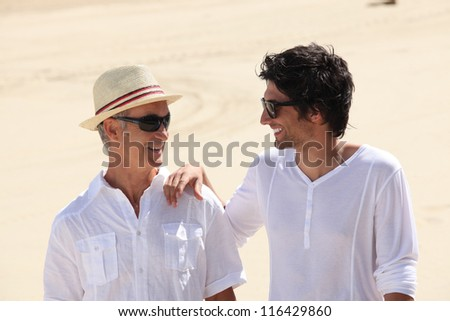Grandfather and grandson on the beach - stock photo