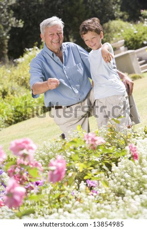 Grandfather and grandson outdoors in garden pointing at plants and smiling