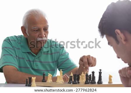 Grandfather and grandson playing chess - stock photo