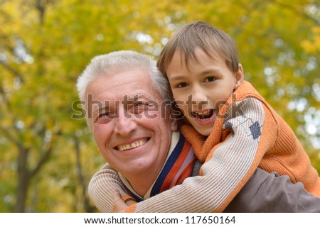 grandfather and grandson playing in autumn park