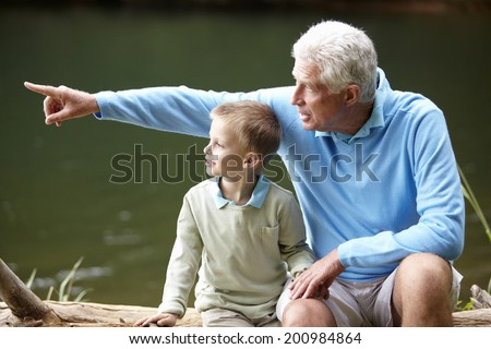 Grandfather and grandson sitting by lake - stock photo