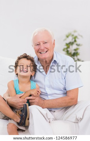 Grandfather and grandson sitting on the sofa while smiling