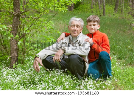 grandfather and grandson with spring flowers in park - stock photo