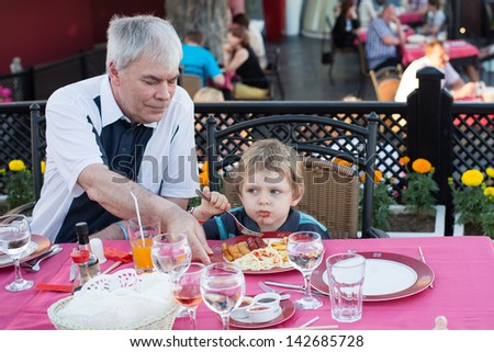 Grandfather and his grandson eating together in summer restaurant - stock photo