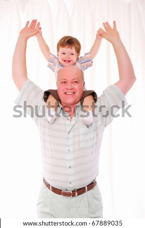 Grandfather and his grandson having fun together. Symbol of the family. - stock photo